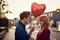 man asking woman out with heart shaped balloon